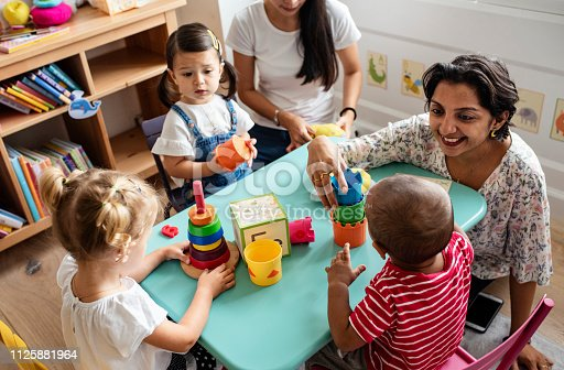 istock Nursery children playing with teacher in the classroom 1125881964