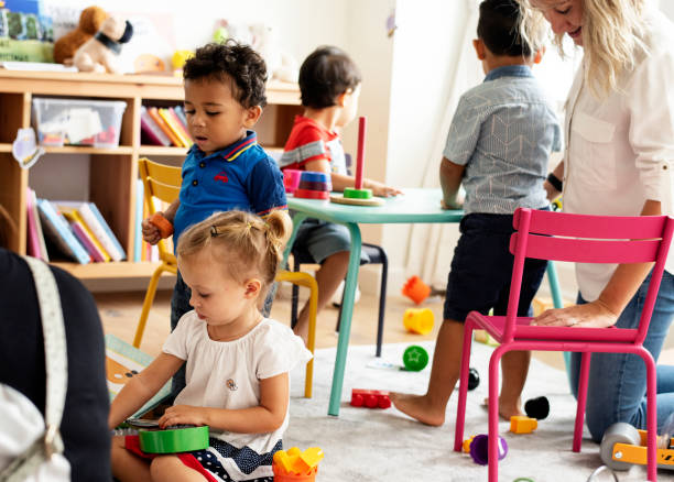 Nursery children playing with teacher in the classroom stock photo