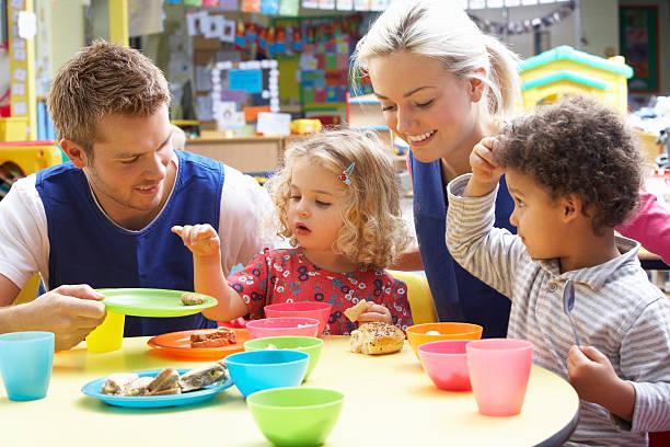 nursery school children having lunch - preschool building stock photos and pictures
