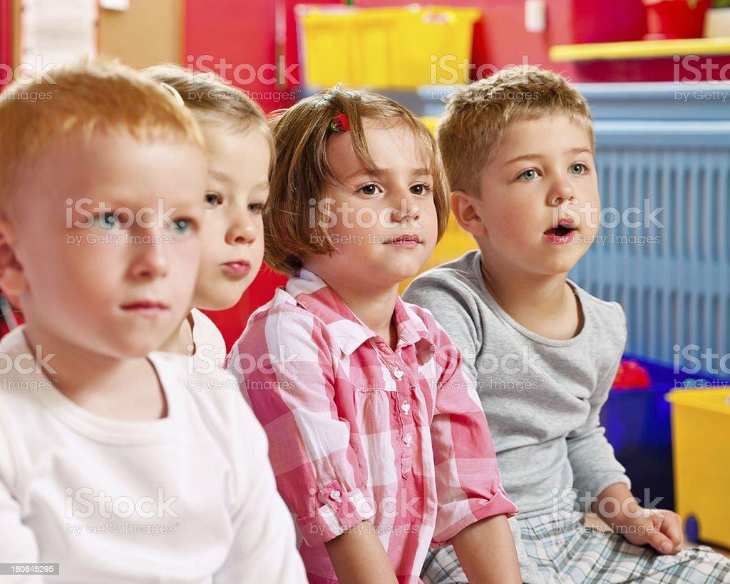 Nursery School Children A serious children sitting in a playroom in a nursery school, looking away. 4-5 Years Stock Photo
