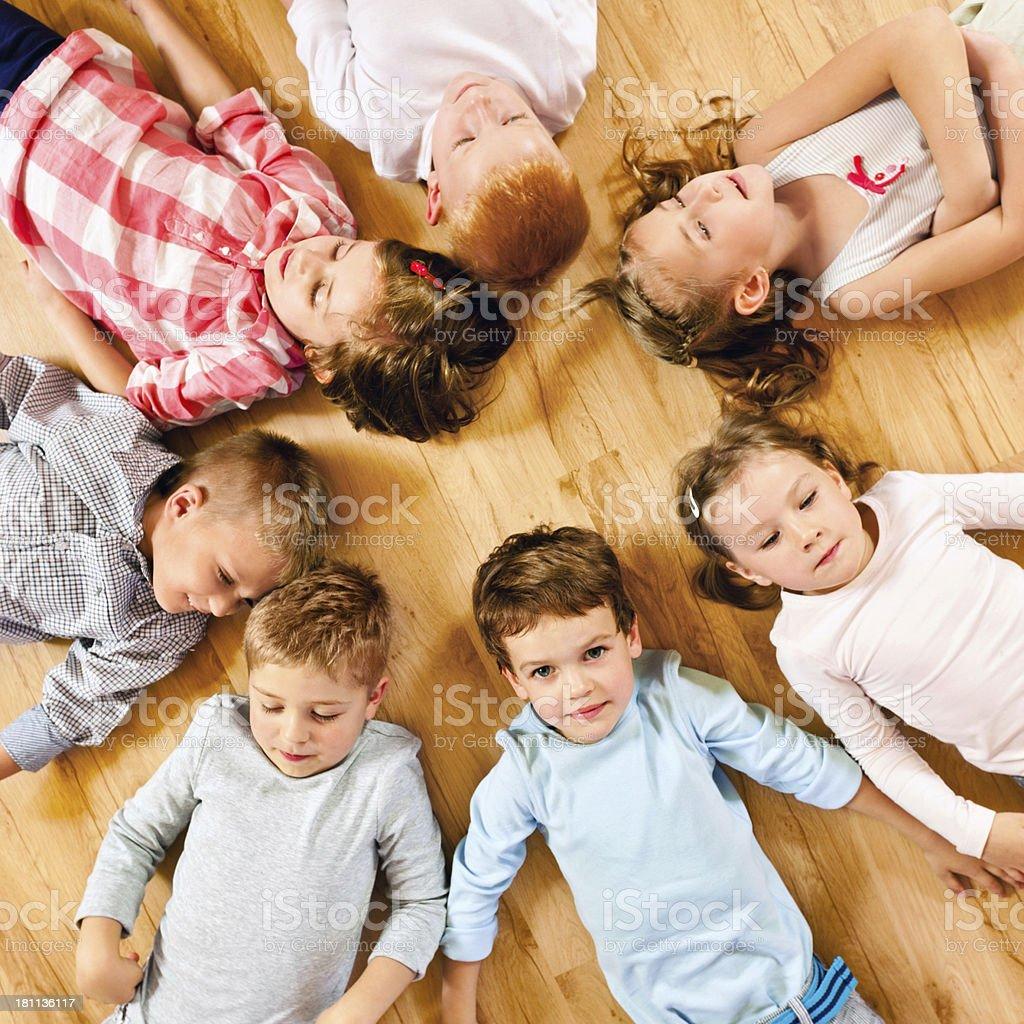 Nursery School Children High angle view of cute nursery school children lying in circle on the floor. 4-5 Years Stock Photo