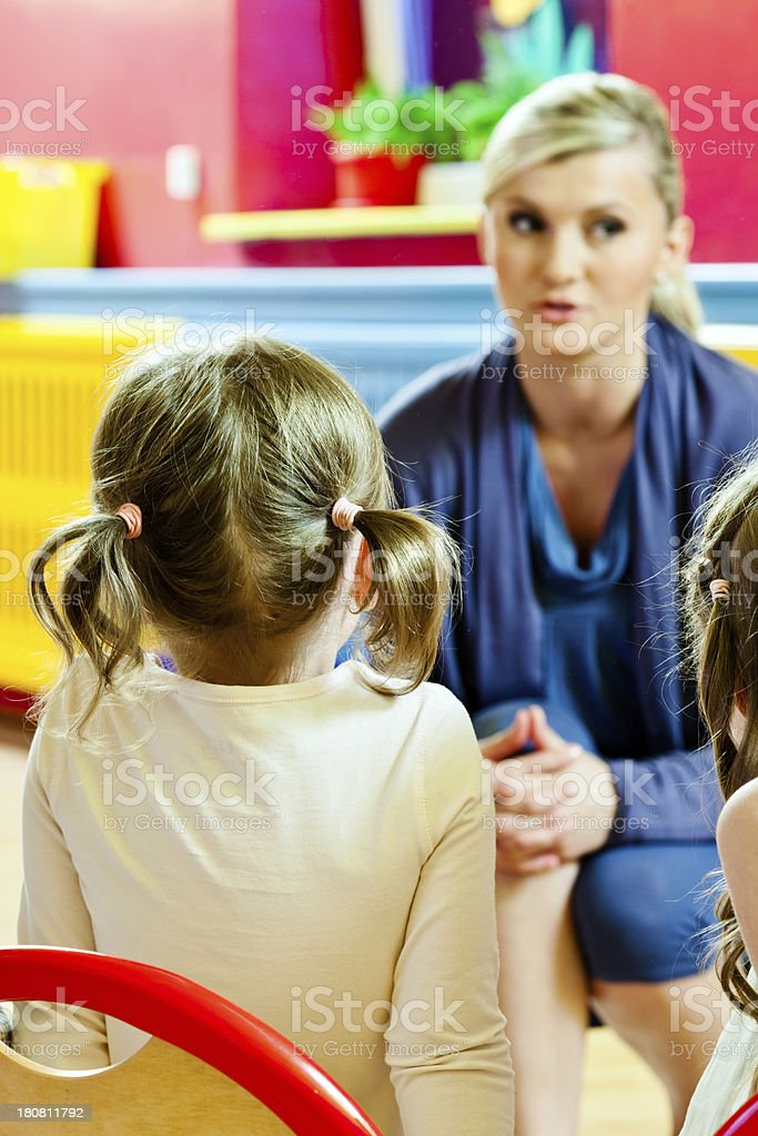 Nursery school Back view of a little girl with ponytails listening to her teacher in a nursery school.  4-5 Years Stock Photo