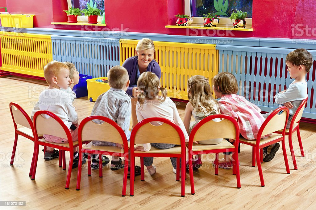 Nursery School A nursery school children sitting on chairs in a playroom and listening to their teacher. One of the children sitting with arms crossed, looks offended 20-24 Years Stock Photo