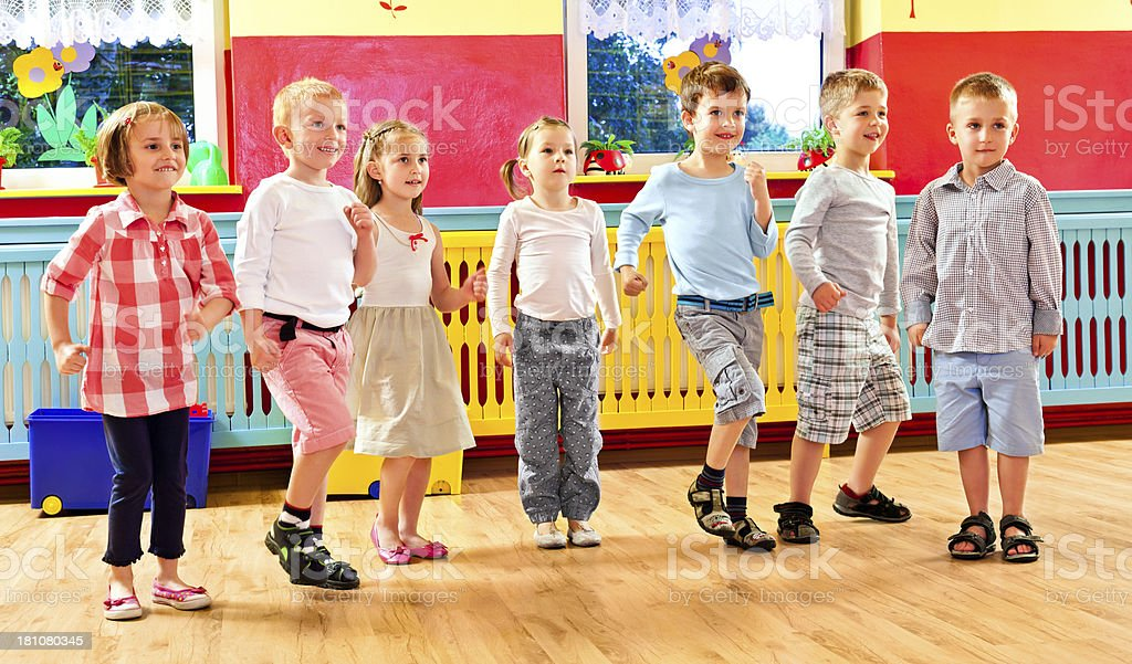Nursery School Group of children dancing together in a playroom in a nursery school. 4-5 Years Stock Photo