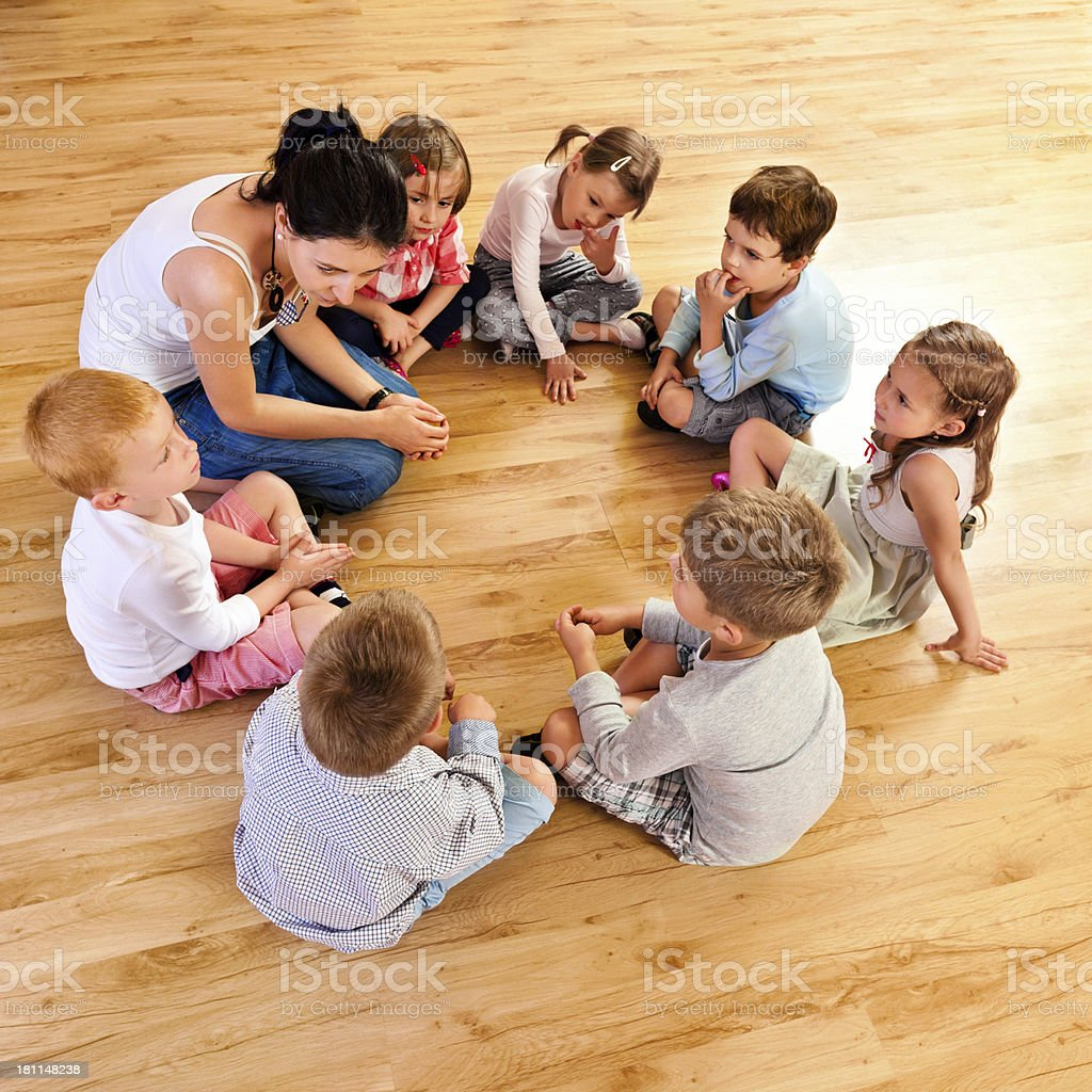 Nursery School Nursery school children sitting in circle on the floor in a playroom and listening to their teacher. High angle view. 25-29 Years Stock Photo