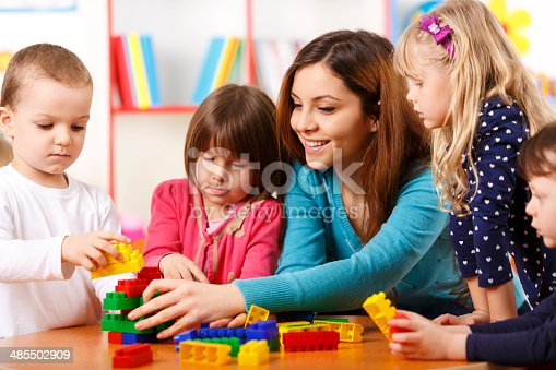 istock Nursery teacher and preschoolers playing with building blocks 485502909