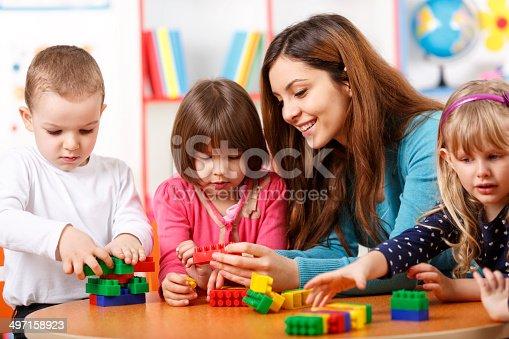 684059604 istock photo Nursery teacher and preschoolers playing with building blocks 497158923