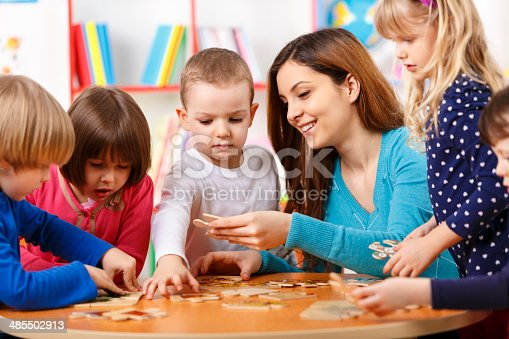 istock Nursery teacher and preschoolers playing with puzzle 485502913