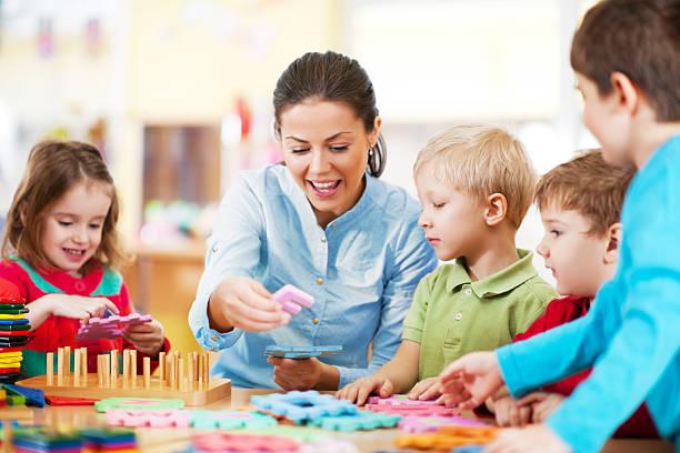 kindergarten lehrer spielen mit kindern - erzieherin stock-fotos und bilder