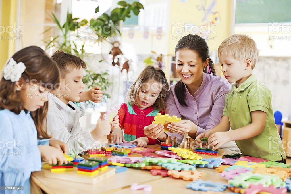 Nursery teacher playing with the kids. royalty-free stock photo