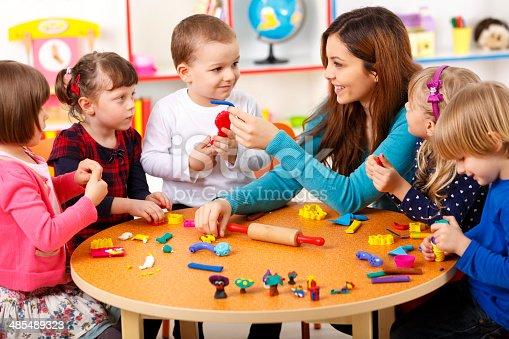 544351868 istock photo Nursery teacher playing with the kids 485489323