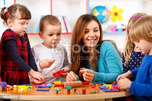 544351868 istock photo Nursery teacher playing with the kids 485489331