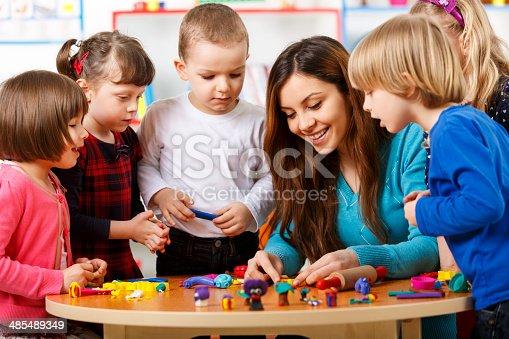 544351868 istock photo Nursery teacher playing with the kids 485489349