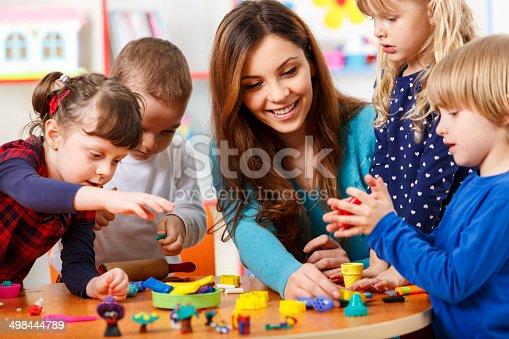544351868 istock photo Nursery teacher playing with the kids 498444789