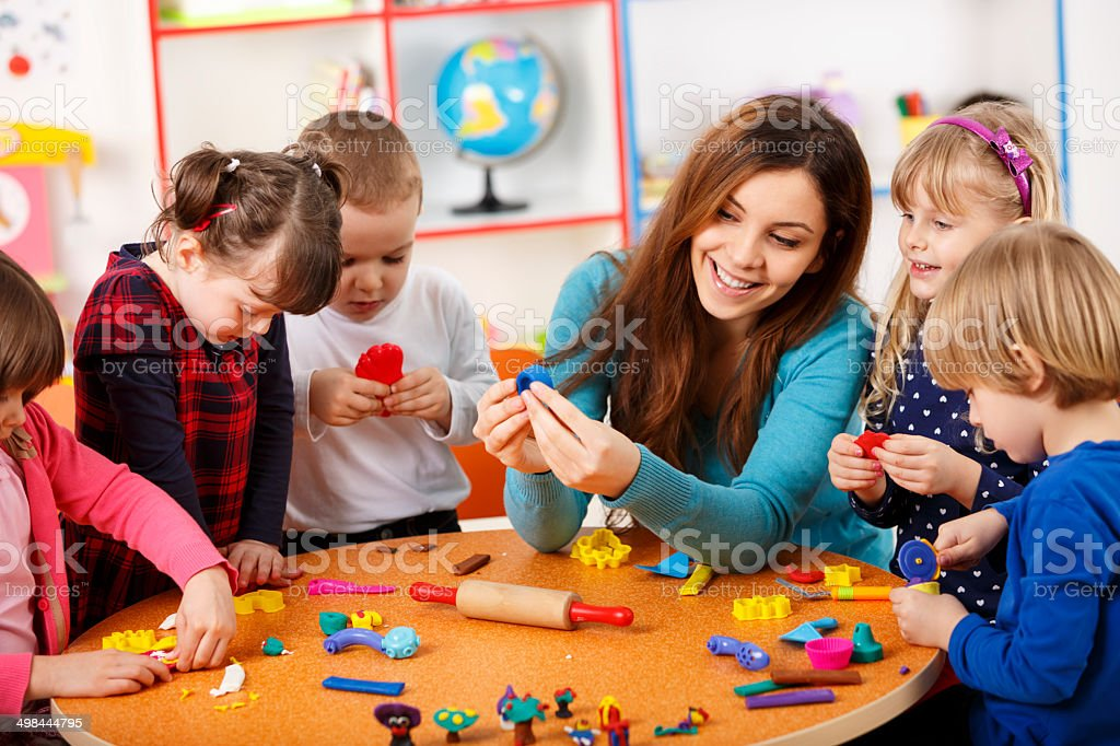 Nursery teacher playing with the kids stock photo