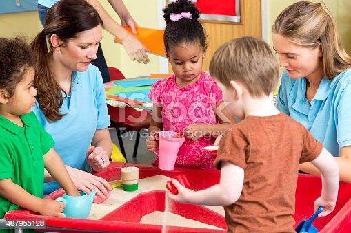 Two young female nursery workers can be seen playing in a sandpit with preschool children, they are all looking content and happy. The image has been shot indoors and in the background there is a table covered in paper.