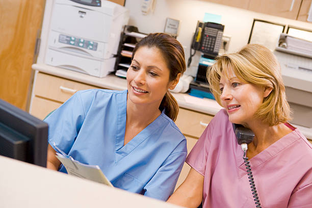 nurses at the reception area in a hospital - nurse on phone stock photos and pictures