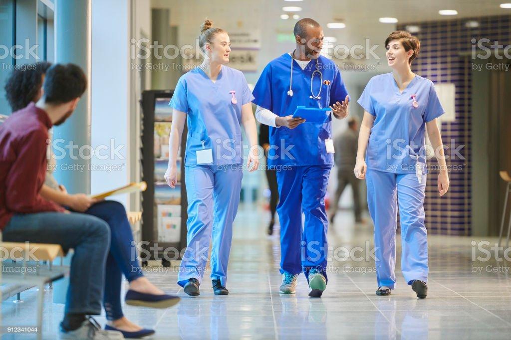 nurses chatting on the way to ward stock photo
