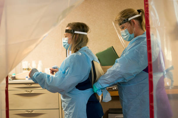 Nurses don PPE to enter quarantined rooms Two blond nurses don PPE protective gear of plastic gowns, face masks, face shields and gloves prior to entering a quarantined patient's room in isolation during the Covid-19 pandemic, Midwest, USA inpatient stock pictures, royalty-free photos & images