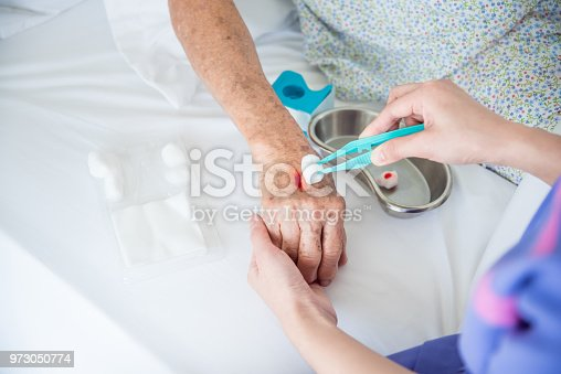 istock Nurse's hands dressing wound for patient's hand 973050774
