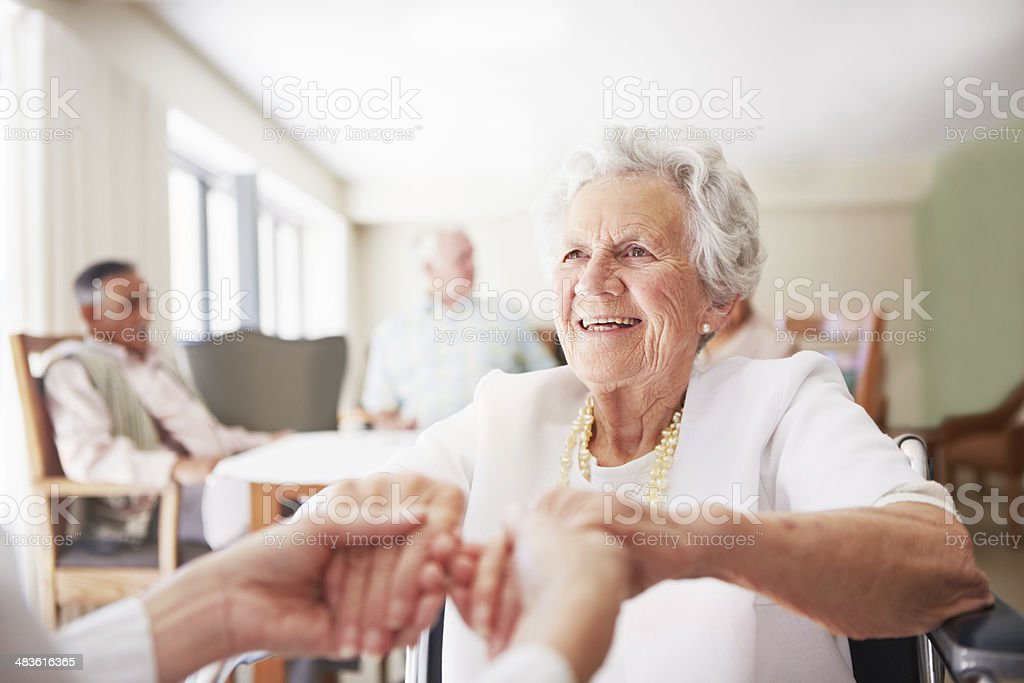 Nurse's hands hold elderly woman's at nursing home royalty-free stock photo
