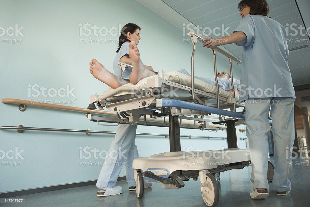 Nurses Moving Patient in Corridor stock photo