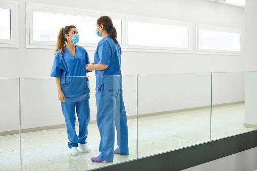 Healthcare workers discussing in corridor. Nurses are in blue uniform during COVID-19. They are in hospital during state of emergency.