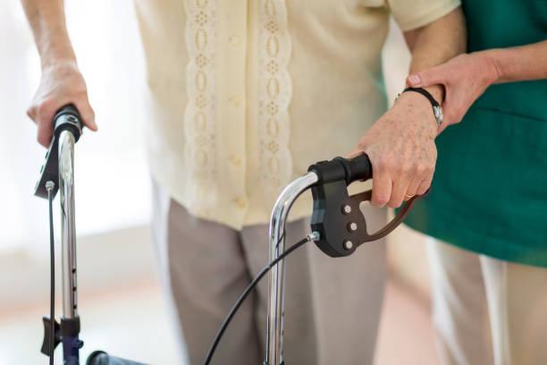 Pflegeassistentin hilft Seniorin mit Gehrahmen – Foto