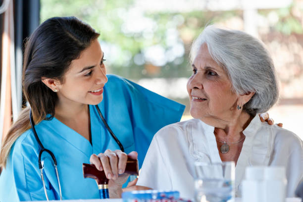 Aide à la maison de soins infirmiers. Jeune docteur féminin hispanique parlant à la femme aînée pendant la visite à la maison. - Photo