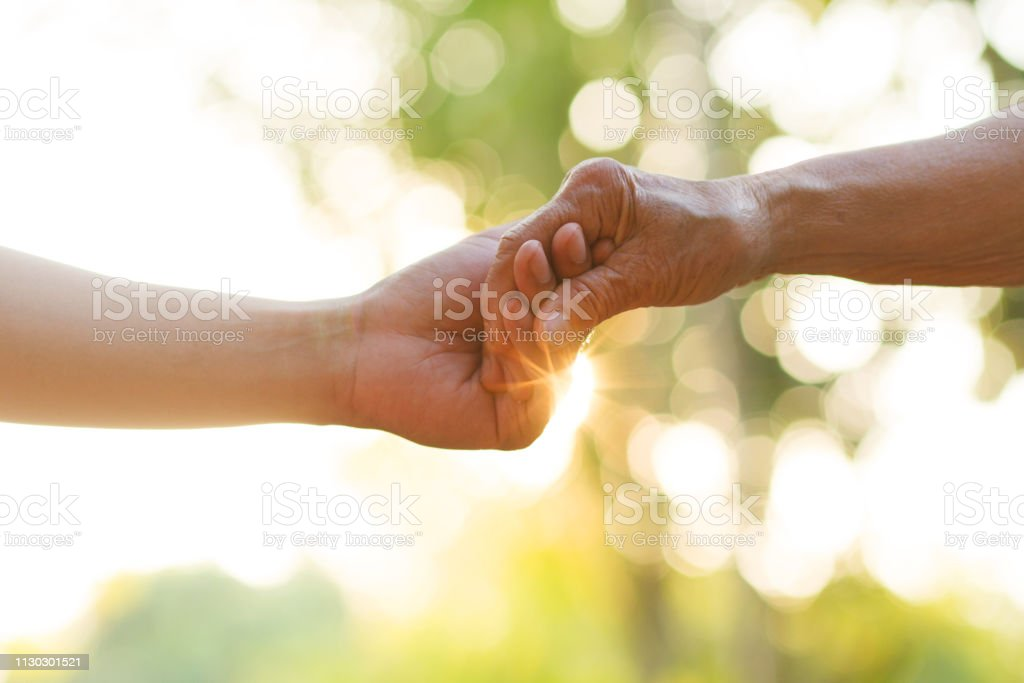 Nursing home help for elderly concept. Hand of young man holds Elder person hand with love. metaphor Support, help, nursing home or help for elderly concept. A Helping Hand Stock Photo