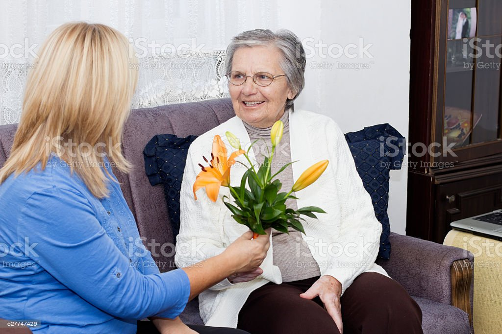 Mature nurse sitting on the sofa and giving to senior woman a bouquet...