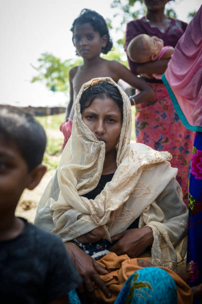 Nursing mother in Rohingya refugee camp in Bangladesh A Rohingya mother breastfeeds her child outside their shelter at Jamtoli refugee camp near Cox's Bazar, Bangladesh (October 26, 2017) rohingya culture stock pictures, royalty-free photos & images