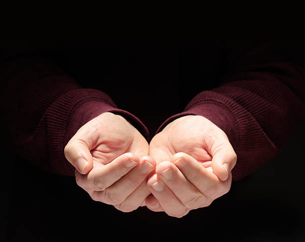 Nurturing Hands Cupped, Empty, Clasped to Hold Something, Black Background Nurturing hands clasped so as to hold something or anything.  The image can be used as is, or you may place whatever you wish above the hands. This image has a million possible uses.  hands cupped stock pictures, royalty-free photos & images