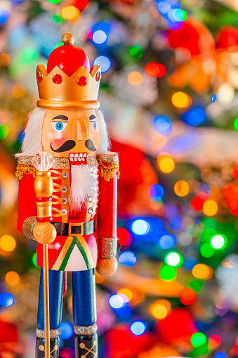 A nutcracker king with a  jeweled crown and scepter stands in front of  a  soft focused decorated Christmas tree .