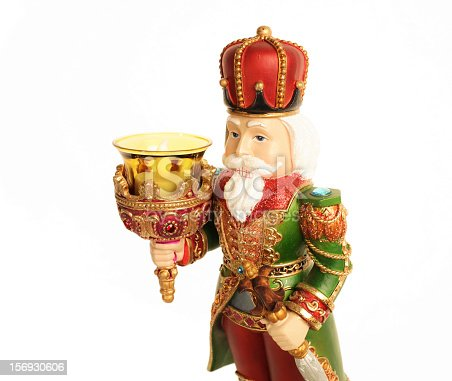 Close-up shot of a Christmas decoration in a shape of a nutcracker, holding a torch (candle holder). Isolated on white.