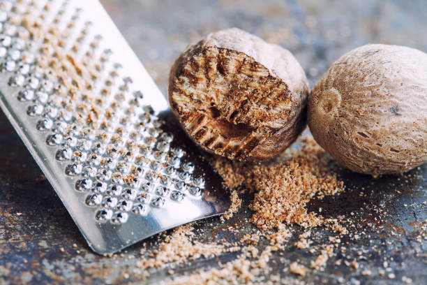Nutmeg grater macro view. Kitchen still life photo close-up muscat nut powder. Shallow depth of field, vintage brown rusty background. Selective focus Nutmeg grater macro view. Kitchen still life photo close-up muscat nut powder. Shallow depth of field, vintage brown rusty background. Selective focus. nutmeg stock pictures, royalty-free photos & images