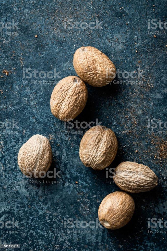 Nutmeg on dark background directly above copy space stock photo