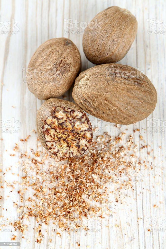 nutmeg on wooden surface stock photo