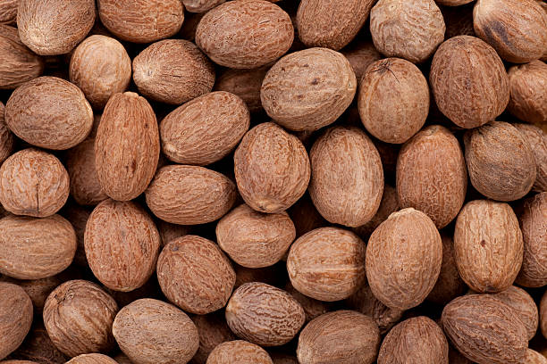 Nutmeg Close up of whole nutmegs as a background.Full Frame. nutmeg stock pictures, royalty-free photos & images