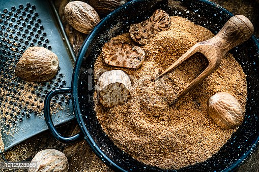 Top view of a rustic wooden table with nutmeg seeds and ground nutmeg. A small grater is beside a container filled with ground and cracked nutmeg seeds. Predominant color is brown. High resolution 42Mp studio digital capture taken with SONY A7rII and Zeiss Batis 40mm F2.0 CF lens