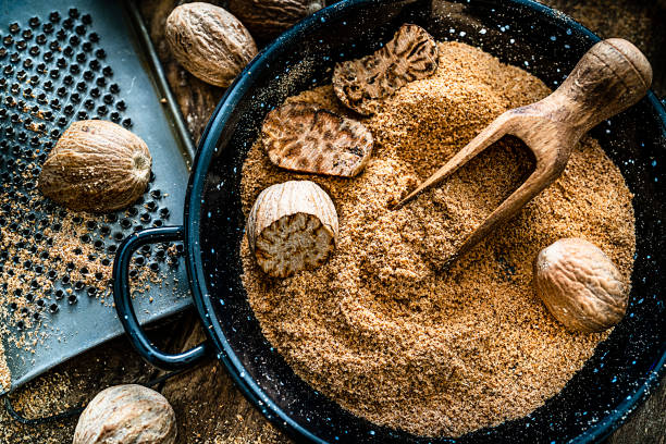 Nutmeg seeds and ground nutmeg shot on rustic wooden table. Top view of a rustic wooden table with nutmeg seeds and ground nutmeg. A small grater is beside a container filled with ground and cracked nutmeg seeds. Predominant color is brown. High resolution 42Mp studio digital capture taken with SONY A7rII and Zeiss Batis 40mm F2.0 CF lens nutmeg stock pictures, royalty-free photos & images