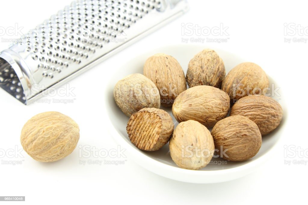 nutmeg seeds in a small white bowl zbiór zdjęć royalty-free