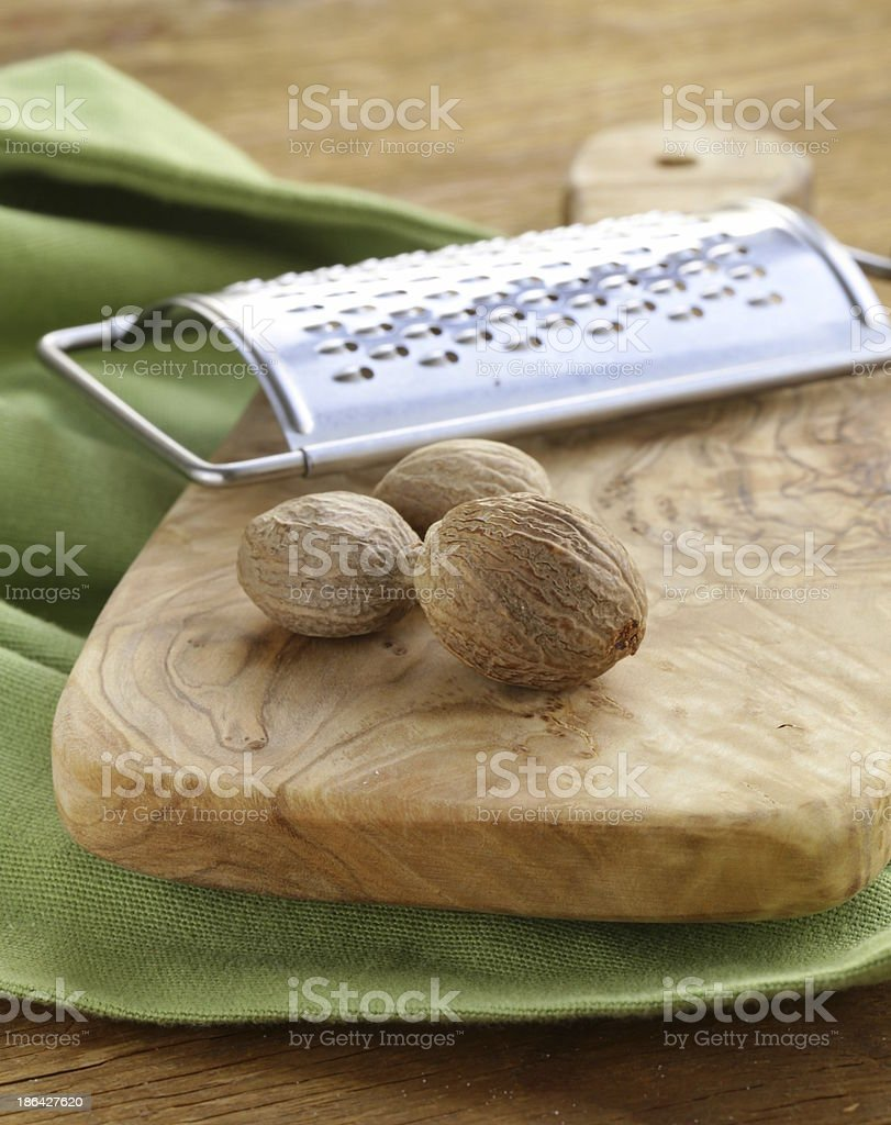 nutmeg whole and grated on a wooden table royalty-free stock photo