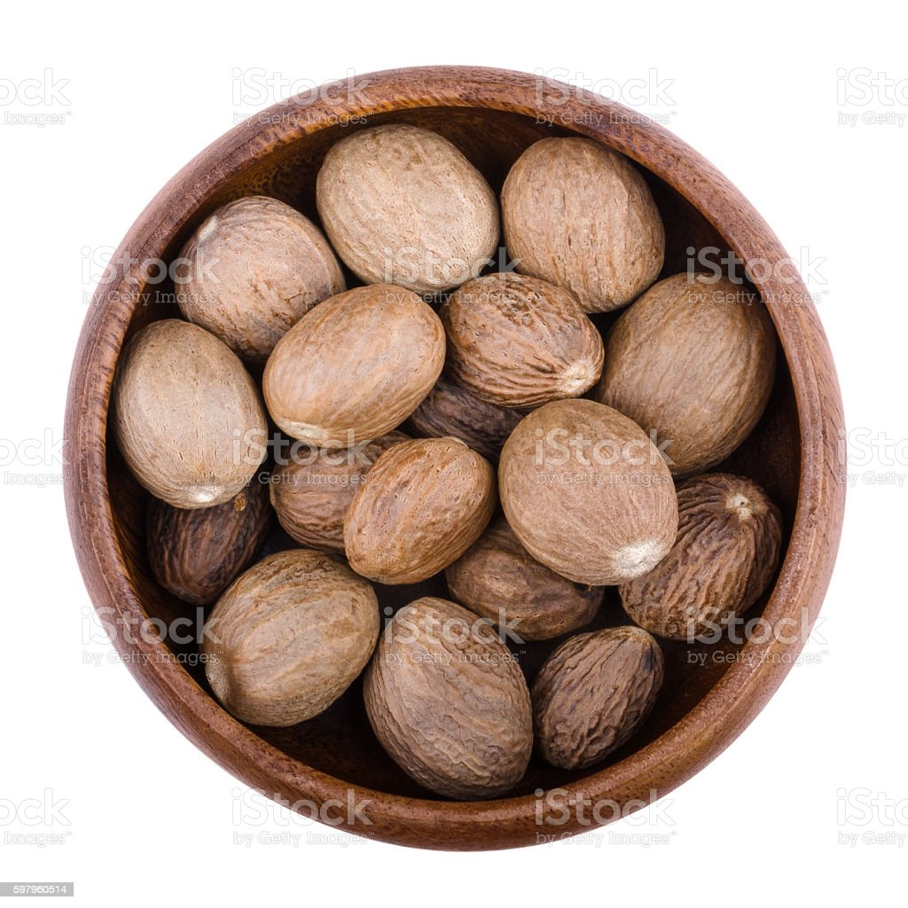 Nutmegs in a bowl over white stock photo