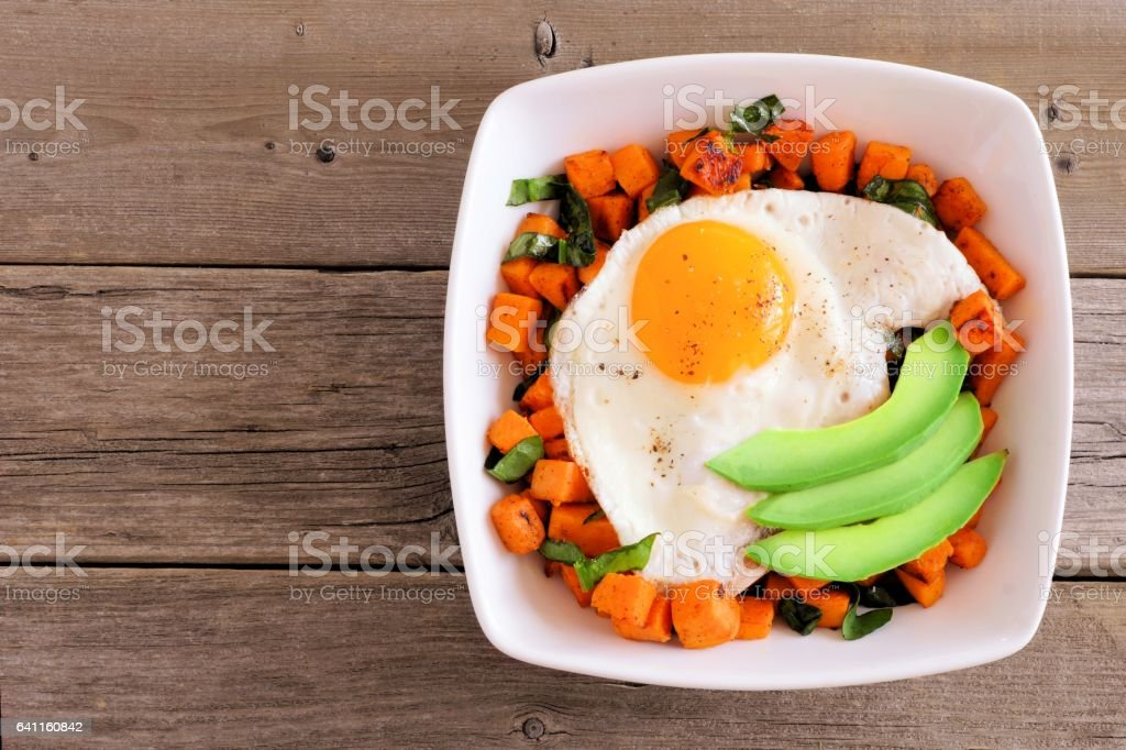 Nutrient bowl with sweet potato, egg, avocado and spinach over rustic wood stock photo