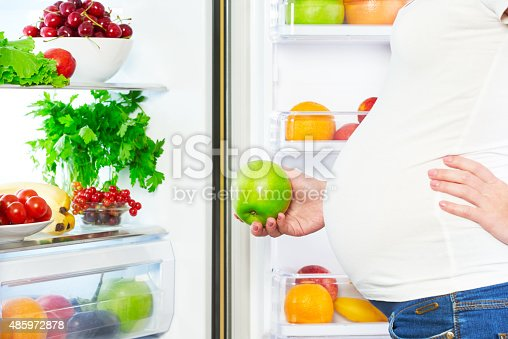 istock nutrition and diet during pregnancy. Pregnant woman with fruits 485972878