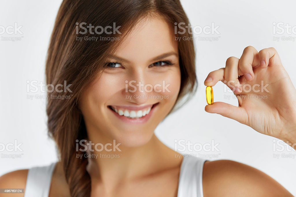 Nutrition. Healthy Lifestyle. Woman Holding Pill With Fish Oil stock photo