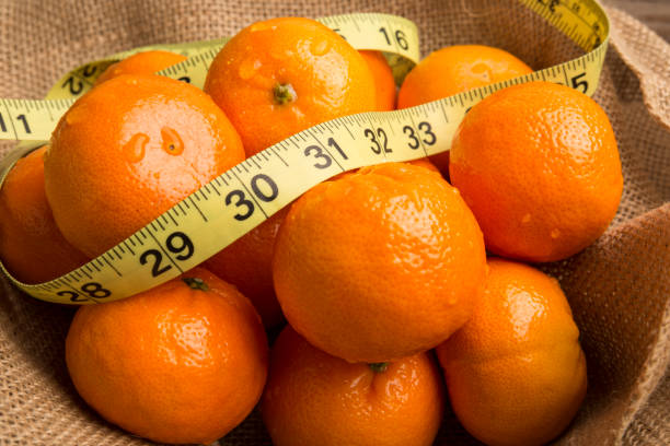 Nutrition Weight loss concept, Bright Healthy organic orange fruit in in burlap with tape measure for weight loss and fiber. Boost immune system stock photo