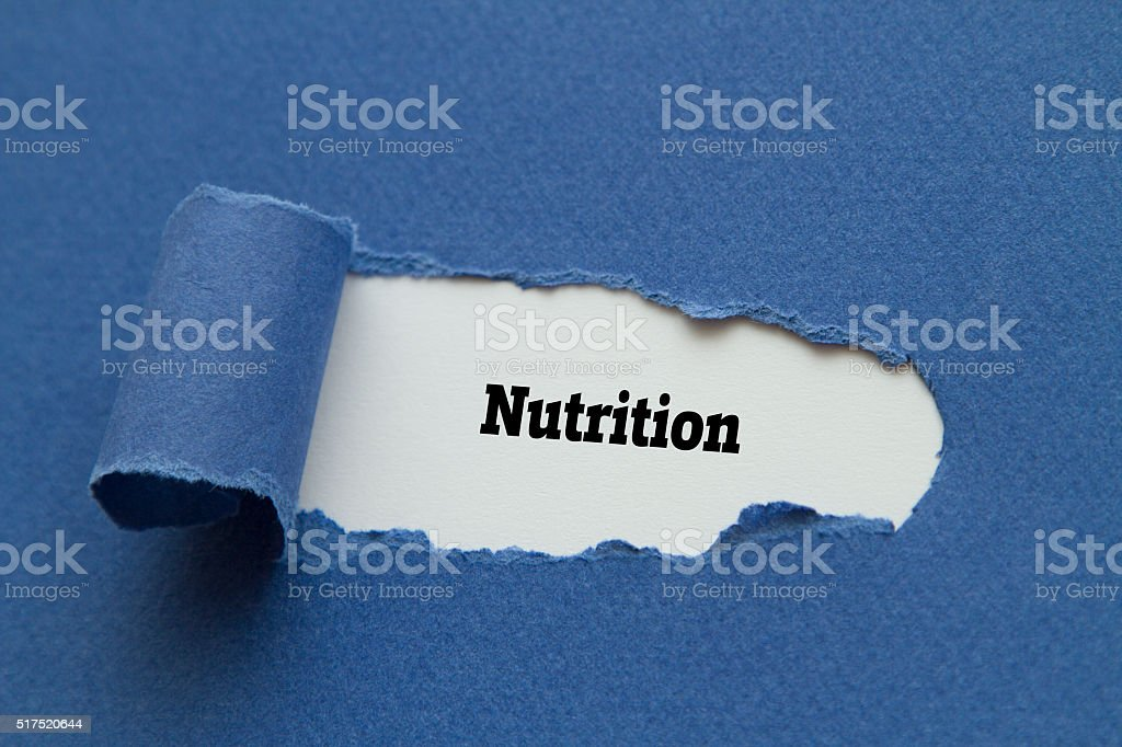 Nutrition word written under torn paper. stock photo