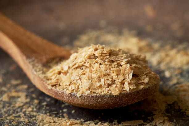 Nutritional brewers yeast flakes Closeup of nutritional brewers yeast flakes in wooden spoon yeast stock pictures, royalty-free photos & images
